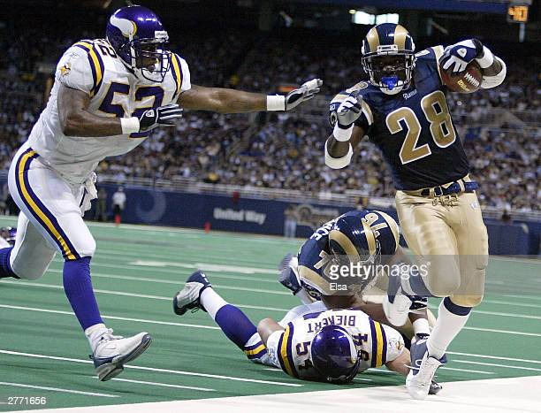Marshall Faulk of the St. Louis Rams is shoved out of bounds by Henri Crockett of the Minnesota Vikings on November 30, 2003 at the Edward Jones Dome...