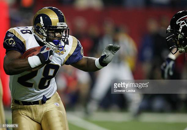 Marshall Faulk of the St Louis Rams runs against the defense of the Atlanta Falcons during the NFC Divisional Playoff game during the NFC Divisional...