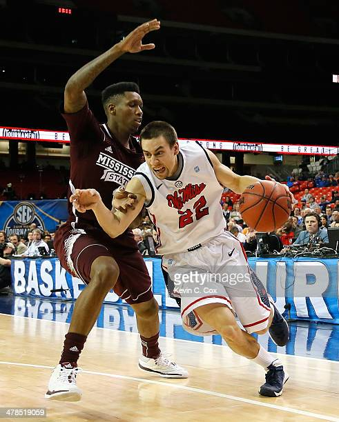 Marshall Henderson of the Mississippi Rebels drives against Fred Thomas of the Mississippi State Bulldogs during the second round of the SEC Men's...