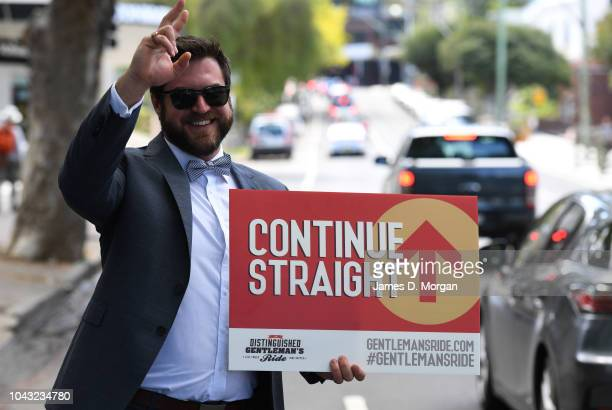 A marshall holds a continue straight sign during the ride on September 30 2018 in Sydney Australia The Distinguished Gentleman's Ride is an annual...