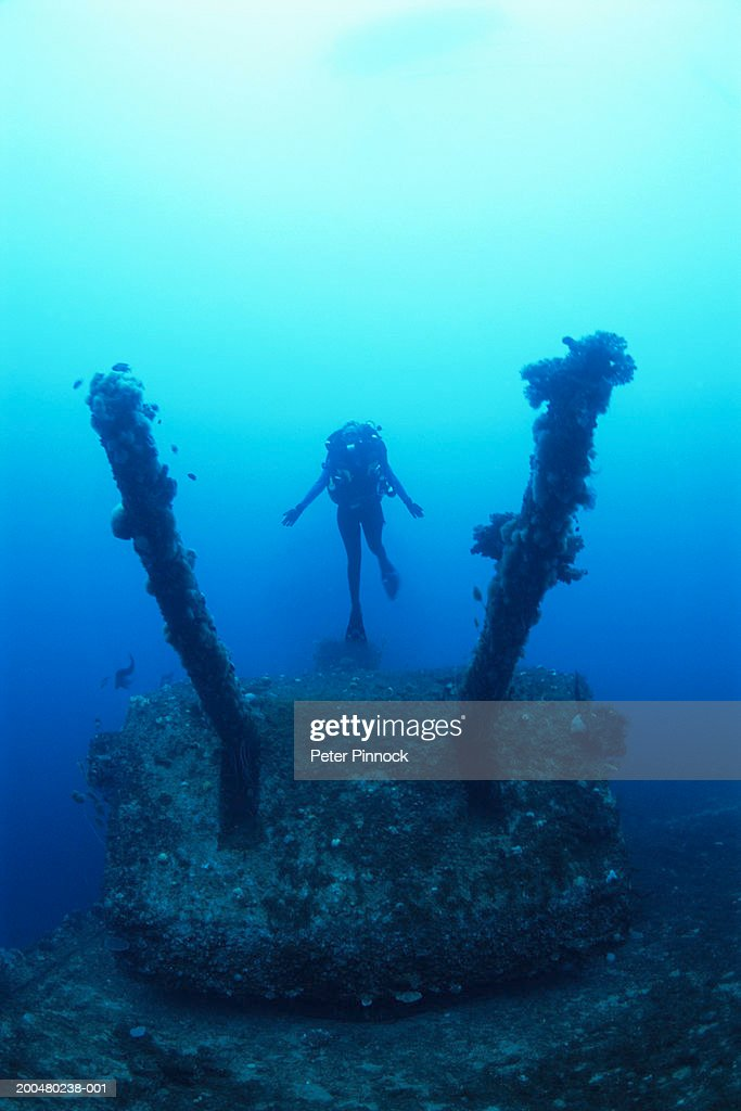 Marshall Islands, female diver exploring aircraft carrier : Stock Photo