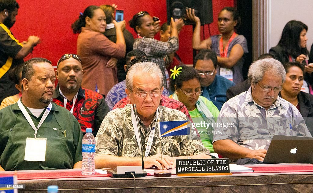 Marshall Islands Foreign Minister Tony de Brum (C) listens to a speaker during the Smaller Islands States Leaders meeting as part of the Pacific Islands Forum in Port Moresby, Papua New Guinea, on September 7, 2015. Vulnerable Pacific island nations will this week send the world an urgent plea for action on climate change at crunch talks in Paris later this year. Some Pacific Islands Forum (PIF) countries lie barely a metre (three feet) above sea level and fear they will disappear beneath the waves without drastic intervention from major polluters. AFP PHOTO / Ness KERTON