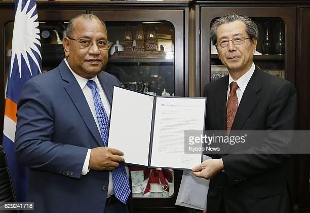 Marshall Islands - Yasuyoshi Komizo , head of the Hiroshima Peace Culture Foundation, presents a letter from Hiroshima Mayor Kazumi Matsui to...