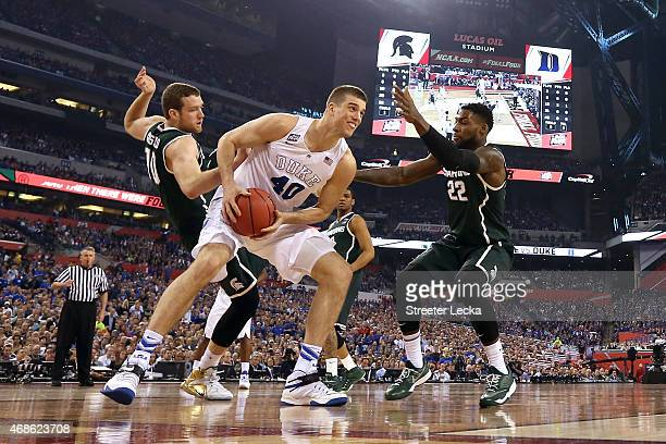 Marshall Plumlee of the Duke Blue Devils handles the ball against Matt Costello and Branden Dawson of the Michigan State Spartans in the first half...