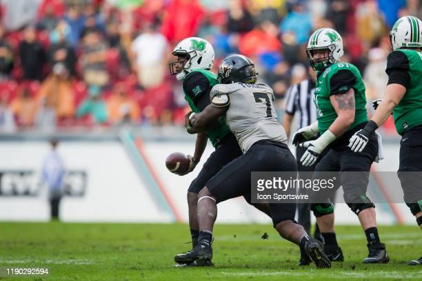 Marshall quarterback Isaiah Green gets rid of the ball as he is tackled by University of Central Florida lineman Kenny Turnier during the Gasparilla...