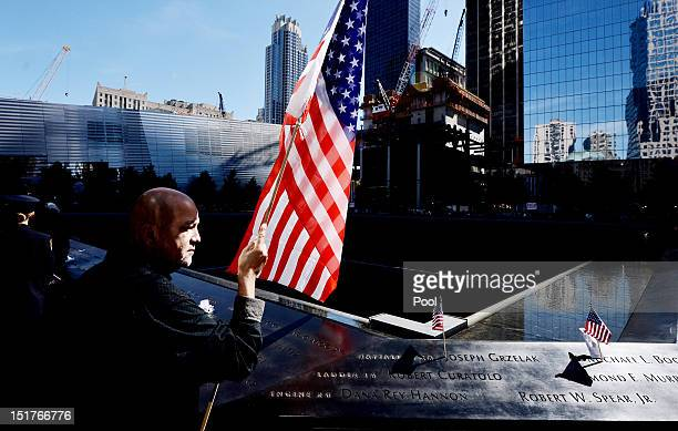 Marshall Rodriguez of New York holds an American flag at the edge of the South Pool while visiting the names of friends he lost during memorial...