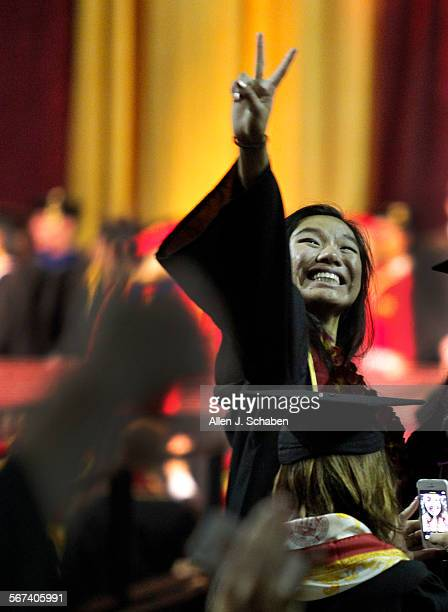Marshall School of Business graduate waves the 'fight on' sign to family and friends before receiving her diploma and listening to the commencement...