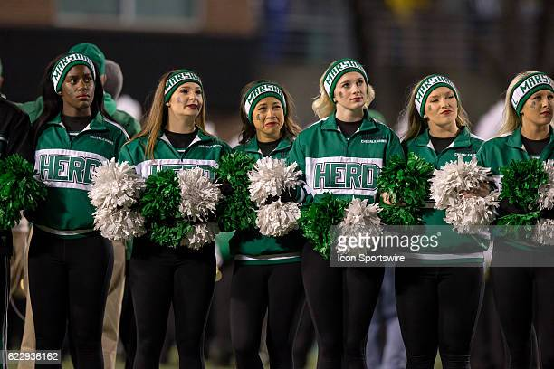 Marshall Thundering Herd cheerleaders react as a video saluting the 1970 team that was killed in a plane crash is shown on the scoreboard prior to...