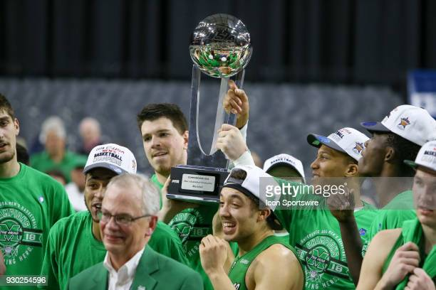 Marshall Thundering Herd players hold the trophy after winning the Conference USA Basketball Championship game between the Western Kentucky...