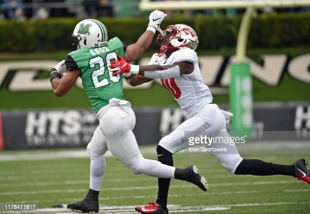 Marshall Thundering Herd running back Joseph Early stiff arms Western Kentucky Hilltoppers defensive lineman DeAngelo Malone during a college...
