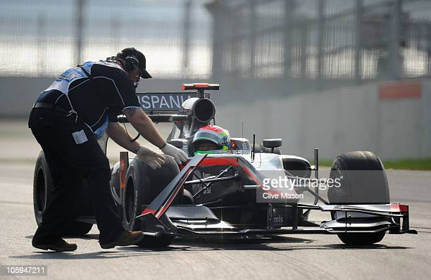 Marshalls attend to the car of Sakon Yamamoto of Japan and Hispania Racing Team during practice for the Korean Formula One Grand Prix at the Korea...