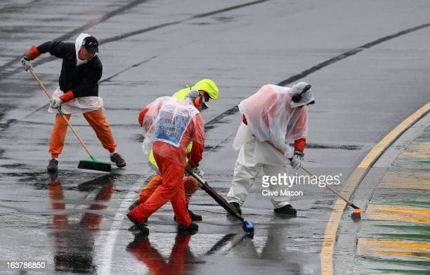 Marshalls clear water from the track during qualifying for the Australian Formula One Grand Prix at the Albert Park Circuit on March 16 2013 in...