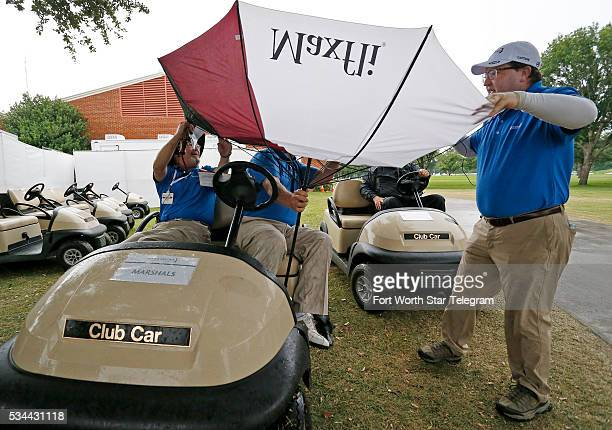 Marshalls Drew Martin, J.R. Rambo and Mark Butler wrestle with Rambo's umbrella during round one of the Dean & DeLuca Invitational Thursday, May 26...