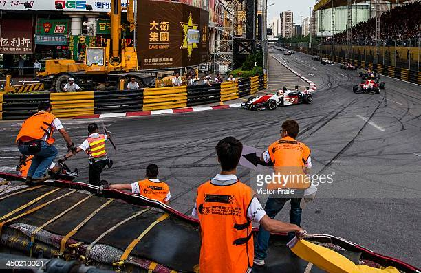 Marshalls jump onto the track to alert cars of a crash at the Lisboa Curve during the Formula 3 event as part of the 60th Macau Grand Prix on...