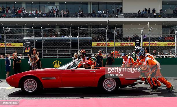 Marshalls push one of the cars into position ahead of the drivers' parade before the Formula One Grand Prix of Mexico at Autodromo Hermanos Rodriguez...