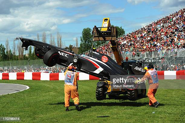 Marshalls recover the damaged car of Esteban Gutierrez of Mexico and Sauber F1 during the Canadian Formula One Grand Prix at the Circuit Gilles...