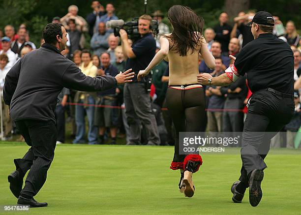 Marshalls try to get their hands on a streaker as golfers Michael Campbell of New Zealand and Paul McGinley of Ireland play the World Match Play...