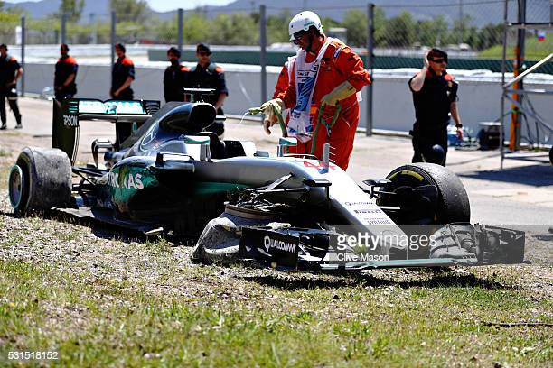 Marshals around the broken car of Lewis Hamilton of Great Britain and Mercedes GP after he crashed on the first lap during the Spanish Formula One...