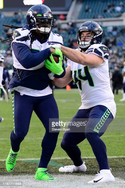 Marshawn Lynch and Nick Bellore of the Seattle Seahawks warm ups before the NFC Wild Card Playoff game against the Philadelphia Eagles at Lincoln...