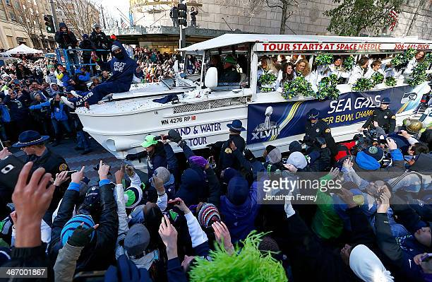 Marshawn Lynch of Seattle Seahawks throws out Skittles to fans during a parade to celebrate their victory in Super Bowl XLVII on February 5 2014 in...