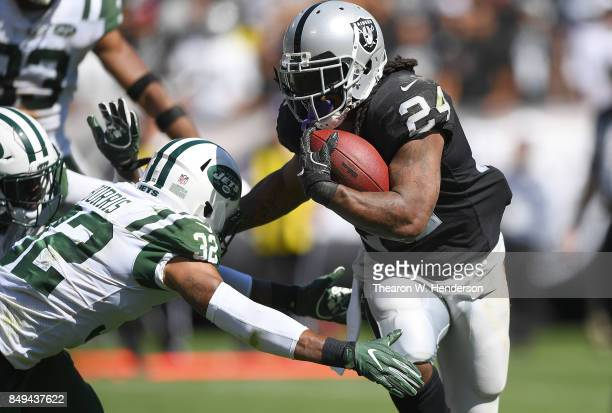 Marshawn Lynch of the Oakland Raiders breaks the tackle of Juston Burris of the New York Jets during the second quarter of their NFL football game at...