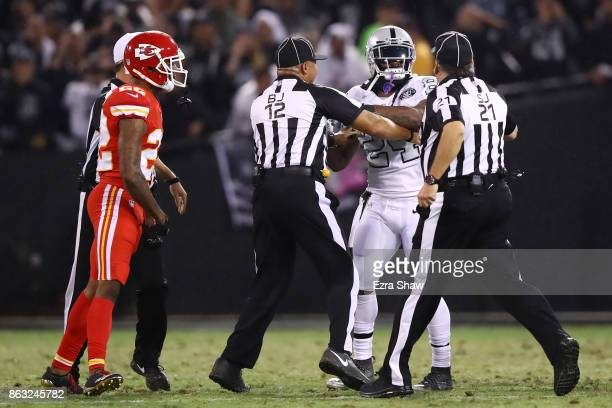 Marshawn Lynch of the Oakland Raiders is restrained after coming off the bench and shoving a referee during a scrum with the Kansas City Chiefs in...