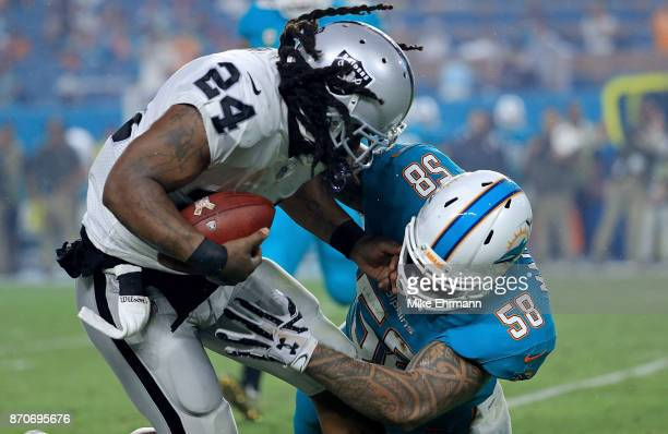 Marshawn Lynch of the Oakland Raiders is tackled by Rey Maualuga of the Miami Dolphins during a game at Hard Rock Stadium on November 5 2017 in Miami...