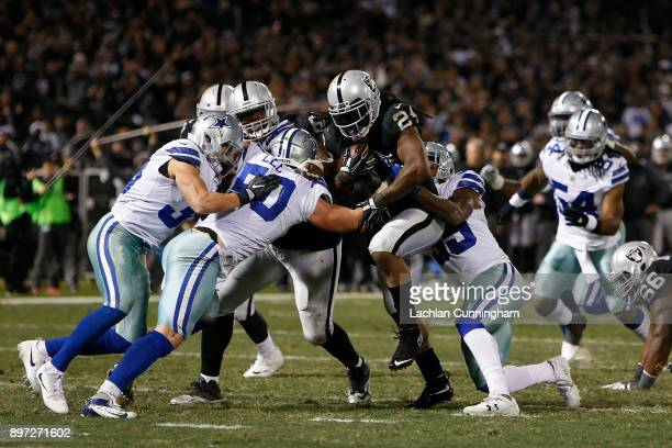 Marshawn Lynch of the Oakland Raiders is tackled by Sean Lee and Kavon Frazier of the Dallas Cowboys at Oakland-Alameda County Coliseum on December...