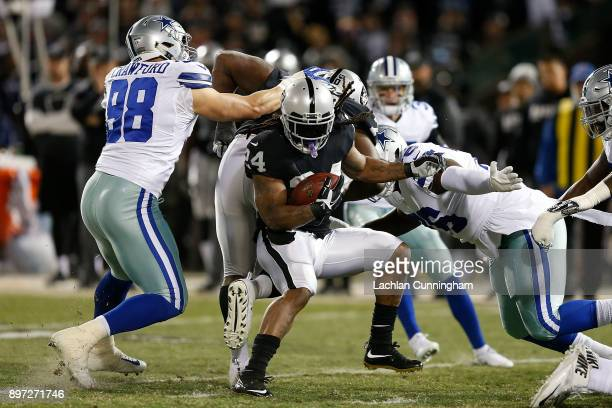 Marshawn Lynch of the Oakland Raiders is tackled by Tyrone Crawford and Richard Ash of the Dallas Cowboys at Oakland-Alameda County Coliseum on...