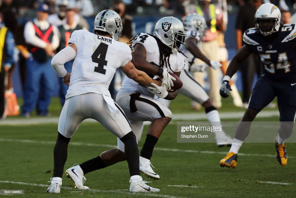 Marshawn Lynch #24 of the Oakland Raiders receives the handoff from Derek Carr #4 of the Oakland Raiders during the game against the Los Angeles Chargers at StubHub Center on December 31, 2017 in Carson, California.