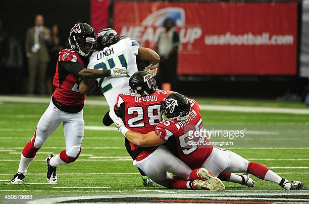 Marshawn Lynch of the Seattle Seahawks carries the ball against Desmond Trufant Thomas DeCoud and Paul Worrilow of the Atlanta Falcons at the Georgia...