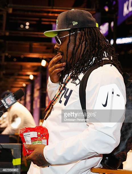 Marshawn Lynch of the Seattle Seahawks eats Skittles as he addresses the media at Super Bowl XLIX Media Day Fueled by Gatorade inside US Airways...