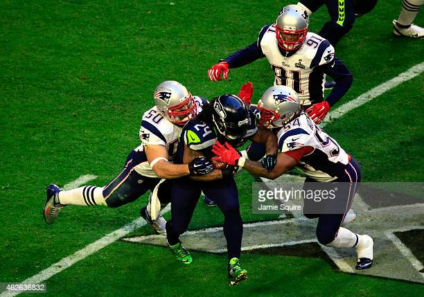 Marshawn Lynch of the Seattle Seahawks is tackled by Rob Ninkovich and Dont'a Hightower of the New England Patriots during Super Bowl XLIX at...