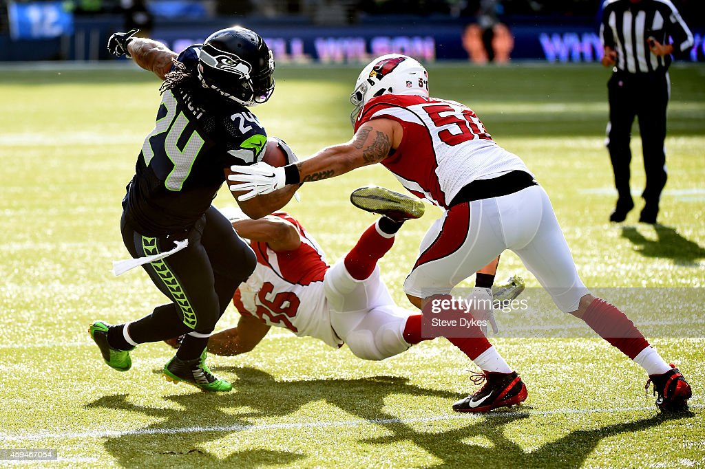 Marshawn Lynch #24 of the Seattle Seahawks runs the ball in the first quarter against Deone Bucannon #36 and Larry Foote #50 of the Arizona Cardinals during their game at CenturyLink Field on November 23, 2014 in Seattle, Washington.