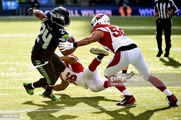 Marshawn Lynch of the Seattle Seahawks runs the ball in the first quarter against Deone Bucannon and Larry Foote of the Arizona Cardinals during...