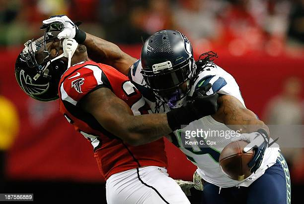 Marshawn Lynch of the Seattle Seahawks stiff arms William Moore of the Atlanta Falcons at Georgia Dome on November 10 2013 in Atlanta Georgia