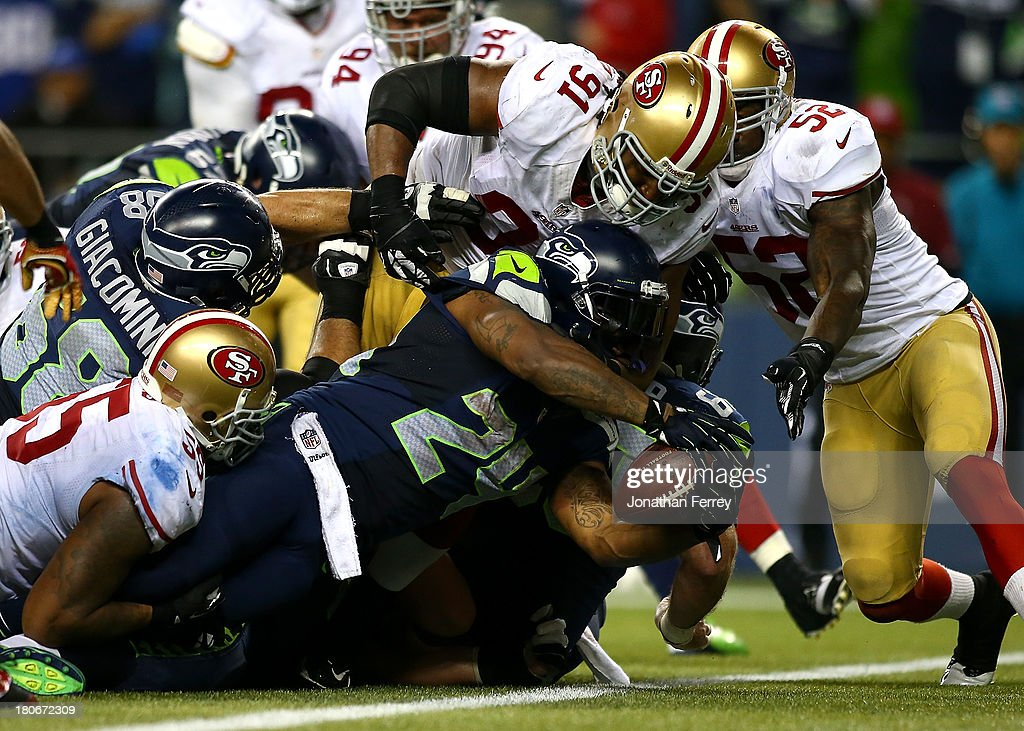 Marshawn Lynch #24 of the Seattle Seahawks stretches the ball across the goal line for a touchdown against the San Francisco 49ers on September 15, 2013 at CenturyLink Field in Seattle, Washington.