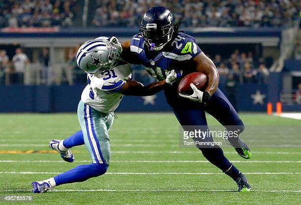 Marshawn Lynch of the Seattle Seahawks takes the ball inside the ten yard line against Byron Jones of the Dallas Cowboys in the fourth quarter at ATT...