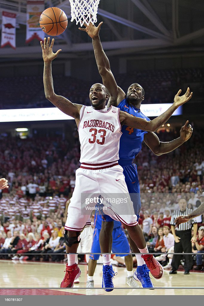 Marshawn Powell #33 of the Arkansas Razorbacks is fouled from behind by Patric Young #4 of the Florida Gators at Bud Walton Arena on February 5, 2013 in Fayetteville, Arkansas.