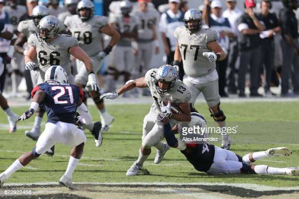 Marshe Terry of the Connecticut Huskies tackles Gabriel Davis of the UCF Knights during a NCAA football game between the University of Connecticut...