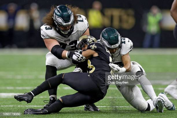 Marshon Lattimore of the New Orleans Saints is tackled by Isaac Seumalo and Nelson Agholor of the Philadelphia Eagles after making an interception...