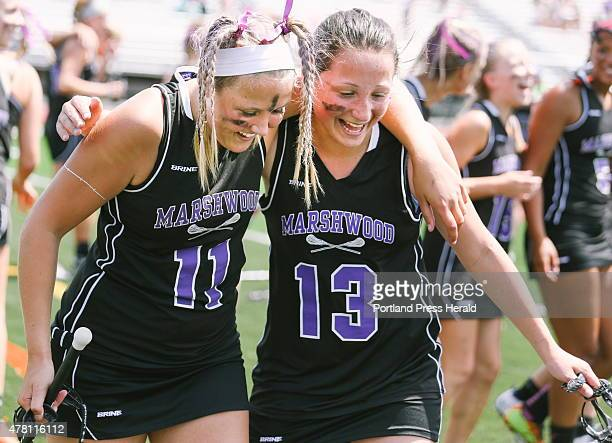 Marshwood players Jenna Kashmer left and Paige Singer embrace after a victory against Messalonskee High School during the Class A girls lacrosse...