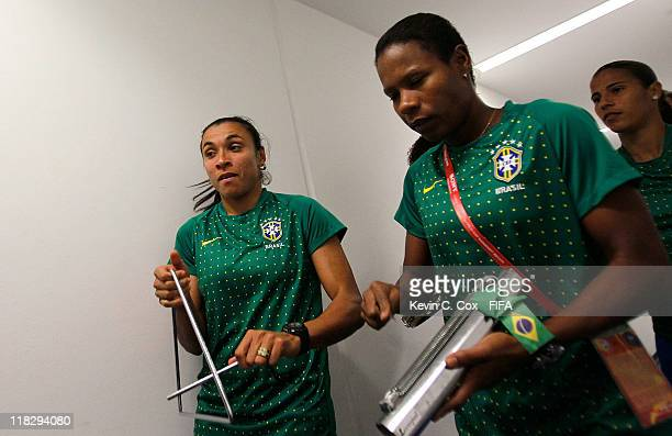 Marta and Formiga of Brazil play instruments as they walk to their dressing room prior to the FIFA Women's World Cup 2011 Group D match between...