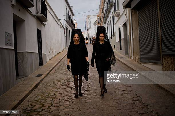 Marta and Itziar wearing mantillas on the way of La Soledad procession for parading as a penitents or dolientes during Good Saturday in Fuente...