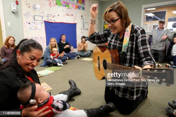 Marta Avina left and son Angel Diaz 6monthold of Concord listen as music therapist Nicole Patton right plays a guitar and sings during a music...