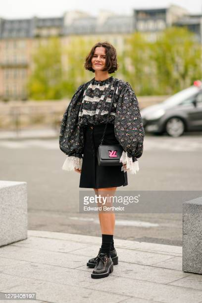 Marta Cygan wears a gray floral print ruffled top with puff sleeves and lace, a black skirt, a black leather Vuitton bag with neon pink logo, black...