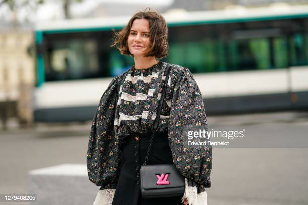 Marta Cygan wears a gray floral print ruffled top with puff sleeves and lace, a black skirt, a black leather Vuitton bag with neon pink logo, outside...