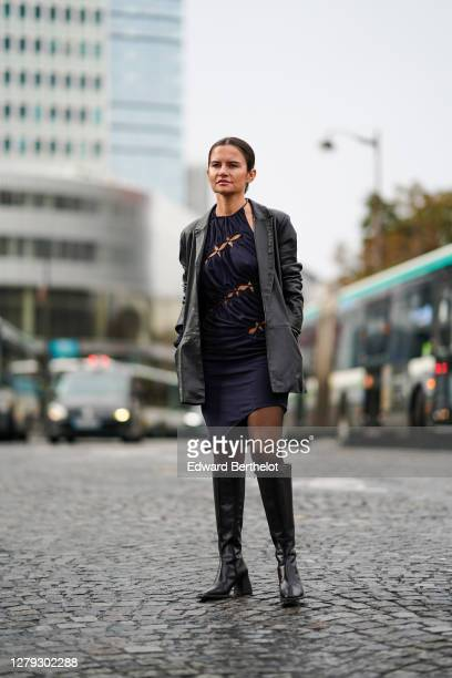 Marta Cygan wears a gray jacket, a dark blue dress, black leather high boots, outside Coperni, during Paris Fashion Week - Womenswear Spring Summer...