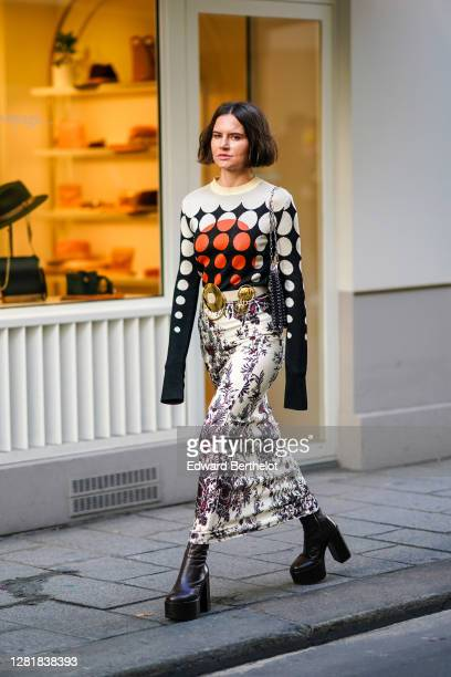 Marta Cygan wears a wool pullover with printed black orange and white dots, a belt with golden buckle, a white floral print colored skirt, leather...
