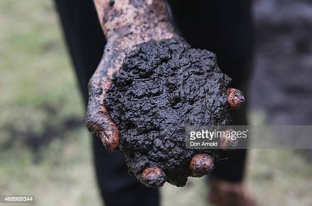 Marta Dusseldorpholds up a handful of mud during a mud fight to raise awareness about the 'Mud Pie Project' to help raise funds to complete the Ian...